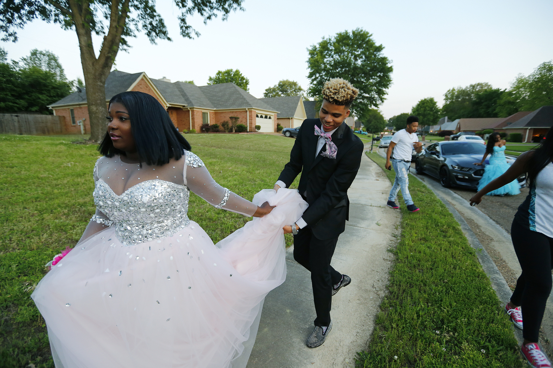 May 6, 2016 - Zearius Jenkins holds Alex Carlton's dress as he picks her up to take her to the Southwind High School prom. After years of going to school together the two became such good friends that they think of each other as siblings. Cartlon was among the original 16 students that crossed over from the St. George's Memphis campus to the Collierville campus but was forced to leave the school after her scholarship was not renewed following the eighth grade. {quote}[St. George's graduates] have more opportunity.{quote} she said. {quote}Southwind doesn't provide as great an opportunity for college. (Mike Brown/The Commercial Appeal)