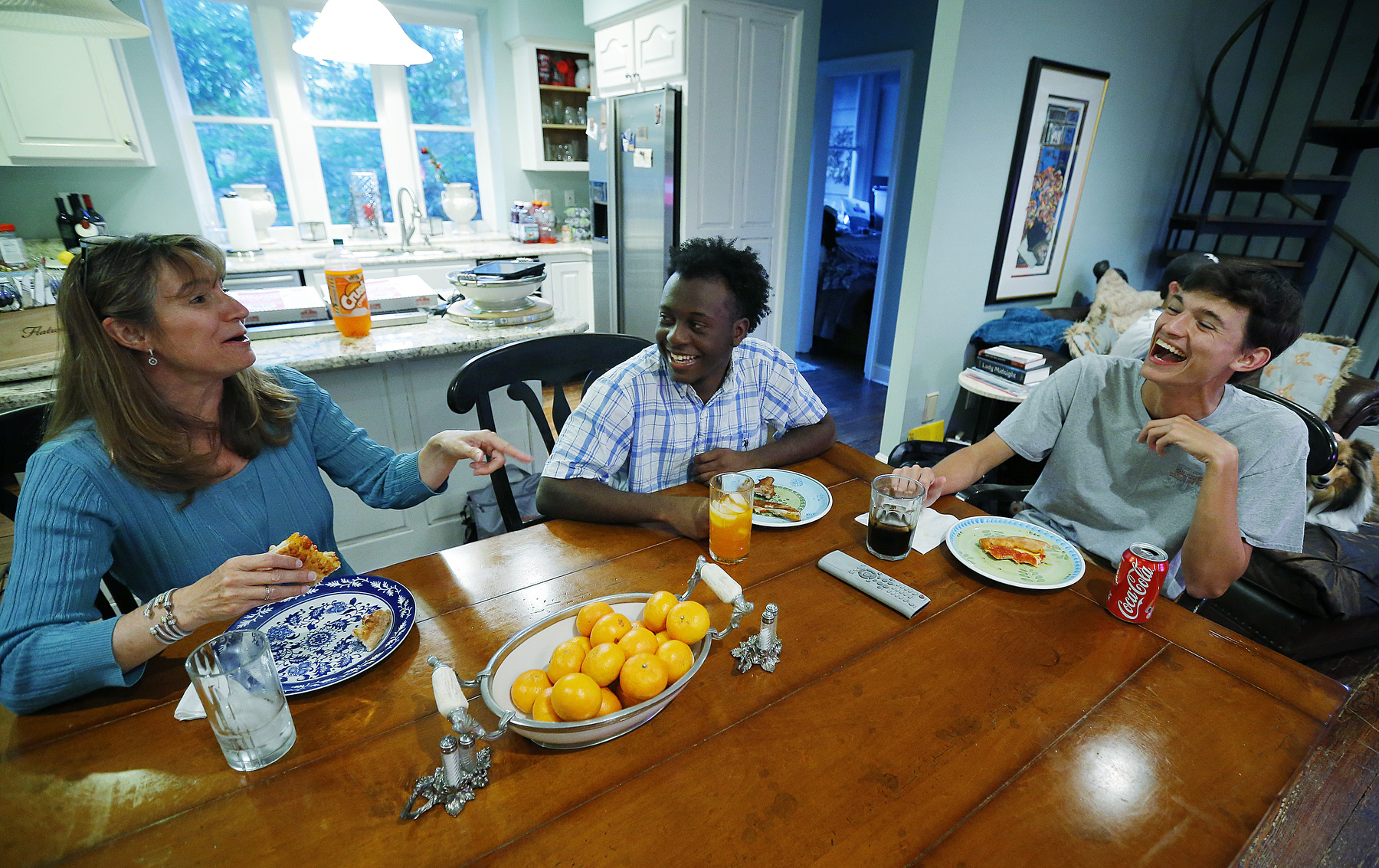 May 10, 2016 - Donovan Borum  (center) shares a laugh at the dinner table with Ann and Carter Burgess. Donovan and Carter were paired together as cross-campus buddies in kindergarten in a program to begin establishing relationships between the primarily white Germantown campus and primarily African-American Memphis campus before the two campuses merged in Collierville for middle and high school. When Borum's family had to relocate to Savannah, Georgia, in October 2014 the Burgess family stepped in and housed him so he could finish his education at St. George's. {quote}They treat me as if I am one of their own.{quote} he said. (Mike Brown/The Commercial Appeal)