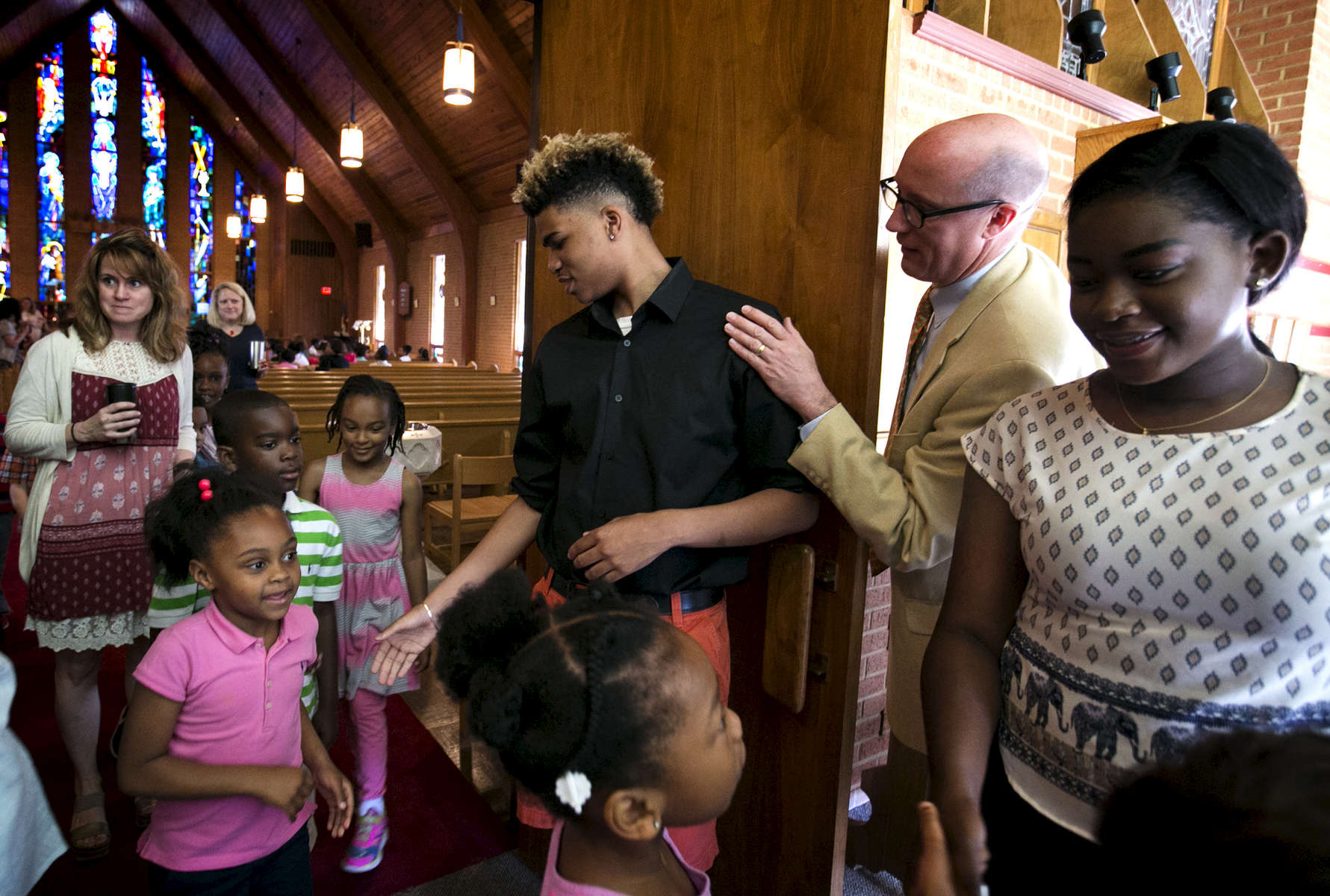May 23, 2016 - St. George's head of school J. Ross Peters taps Zearius Jenkins on the shoulder as Jenkins and Erica Stevenson shake hands with young students following a chapel service at the Memphis campus the day after graduation. {quote}The real work is beginning.{quote} Peters said. {quote}This is the moment when we grow in our full selves. This is the model coming to its first fruition.{quote} Jenkins, Stevenson and a handful of others were among the first students to ever walk the halls at the Memphis campus and are members of the first graduating class under the three-campus model the school began more than a decade ago. (Mike Brown/The Commercial Appeal)