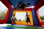 July 18, 2016 - Jim Brown (center), 15, flips inside a bounce house as Martekuz Harris (left), 12, and Jevon Jones, 11, look on during a {quote}Not in My Neighborhood{quote} block party hosted by DeAndre Brown and LifeLine 2 Success. The gathering took place down the street from where a 19-year-old was murdered on the 3500 block of Gowan, as a way to speak out against violence in the community. (Mike Brown/The Commercial Appeal)