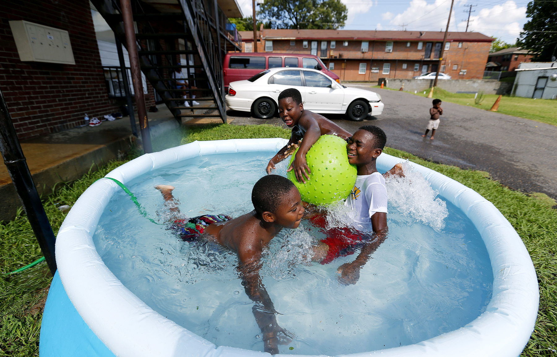 July 26, 2016 - Tarion Johnson, 8, (from left) DeAntonio Jackson, 9, and Royce Jackson, 10, goof off while staying cool in a small pool outside their apartment complex on Danny Thomas near Georgia. According to the National Weather Service the heat index topped 105 degrees. (Mike Brown/The Commercial Appeal)