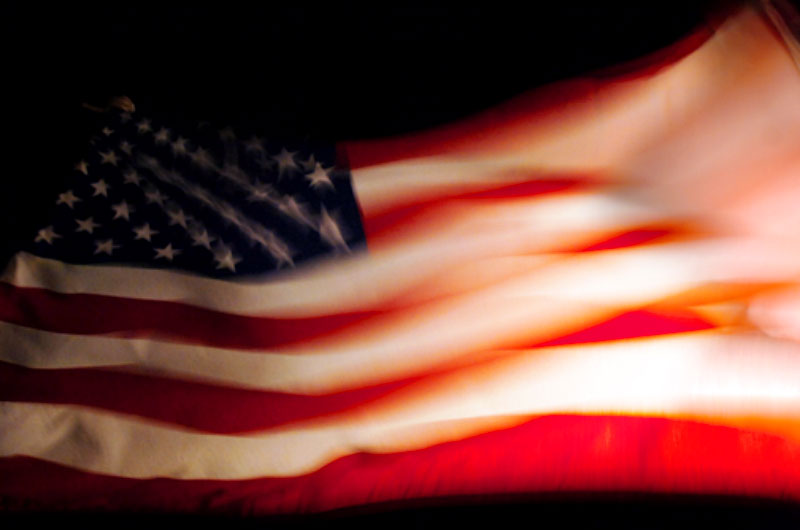 An American flag waves in the breeze on the back of a patrol boat during a night time crossing of the waters within the US Naval Station in Guantanamo Bay, Cuba.(© Mike Brown)