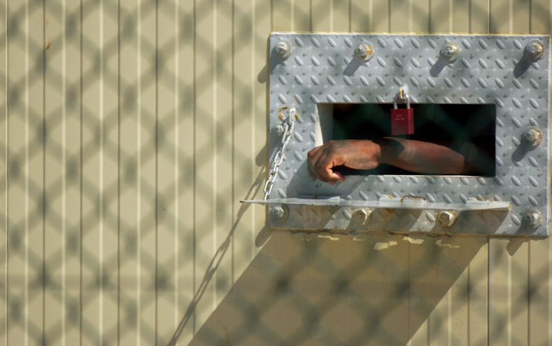 A detainee's arm hangs outside his cell within Camp Delta's Camp 4 medium security prison. The men within Camp 4 are considered compliant, meaning they provided credible information and have conformed to prison rules. As a reward they live, eat and pray in a communal setting.(© Mike Brown)