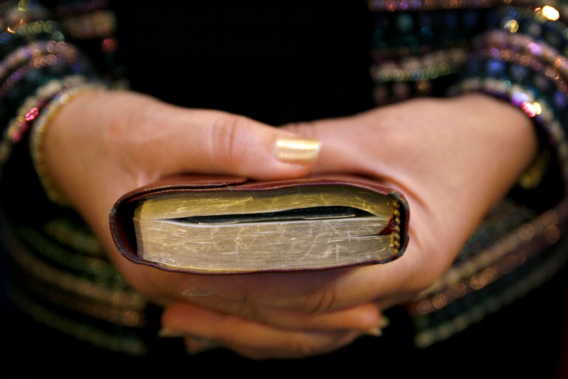 Paulette Holt, from Carson, CA, clasps her bible during the opening of the Order of Divine Worship at the FedEx Forum on Sunday.(Mike Brown/Memphis Commercial Appeal)
