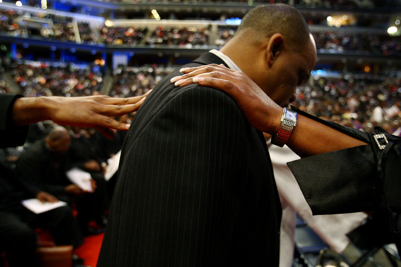 Saints lays their hands on the shoulder of Danny Morris, from Washington D.C., while they pray over him during the official day service of the 102nd Holy Convocation held at FedExForum.