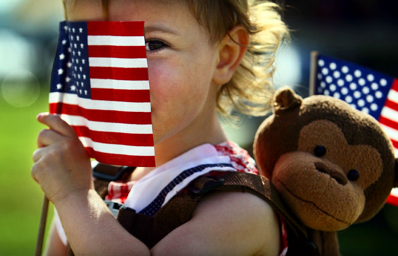 Briley Whitehead, 2, of Baileyton, AL, plays peekaboo from behind her flag in Tom Lee Park while waiting for the big fireworks display to light up the sky on the Fourth of July. (Mike Brown/Memphis Commercial Appeal)