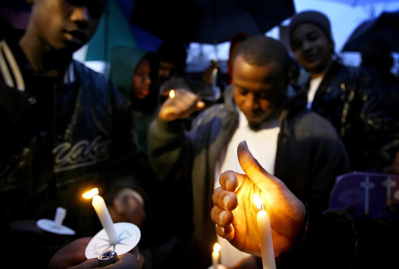 A gang member shields his candle from the wind and rain outside the National Civil Rights Museum during a candle light vigil to honor victims of violence as part of the Southern Christian Leadership Conference event on the eve of Martin Luther King Day. Individuals from the four major black gangs operating in Memphis attended.(Mike Brown/ Memphis Commercial Appeal)