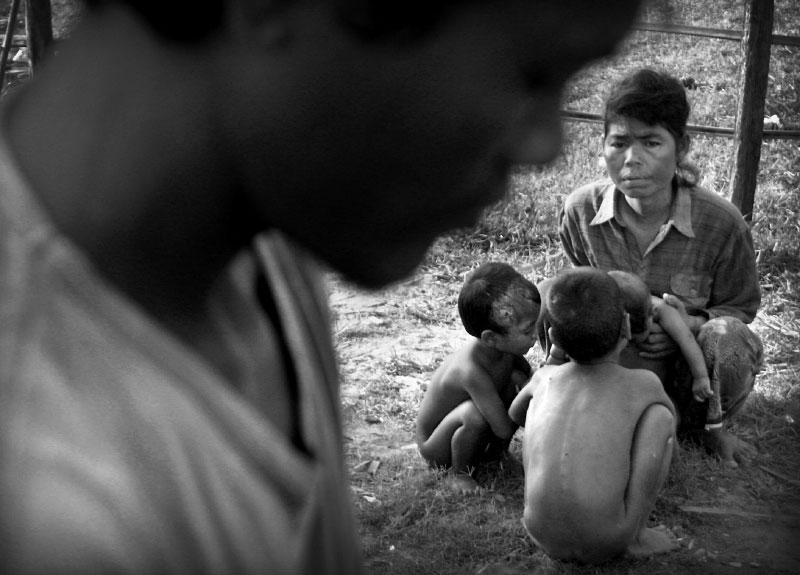Jen Chenda, wife of land mine victim Jen Kina, looks up at him while sitting with three of the family's five children, (l-r) Miss Pe, 5, Peap, 7, and their yet to be named 5 month-old. The government has failed to pay Kina's $20 per month pension which has forced him to beg on the streets in order to provide a marginal existence for his family.(© Mike Brown)
