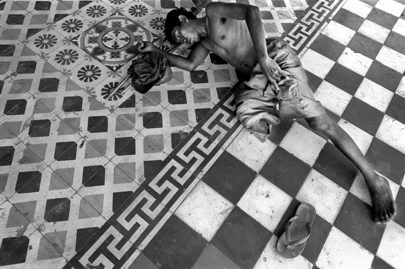 A homeless man sleeps on the floor outside a watt in Siem Reap. The lack of training and available jobs for amputees leaves many land mine victims impoverished and homeless. Buddhist monks often provide shelter and food for those in need.  (© Mike Brown)