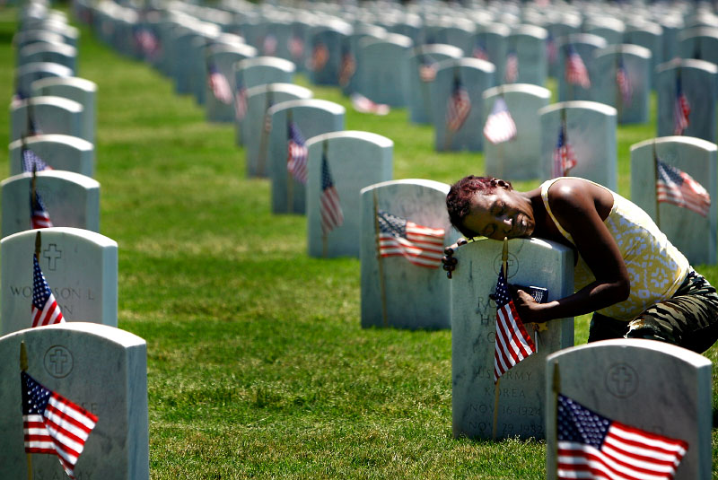 May 29, 2011 - Mary Coleman weeps as she embraces the headstone marking the grave of her mother and father, Robert and Mary Cole, at the Memphis National Cemetery on Sunday. Her father served in the Korean war with the Army. The cemetery hosted its annual Memorial Day Service on Sunday.(Mike Brown/The Commercial Appeal)