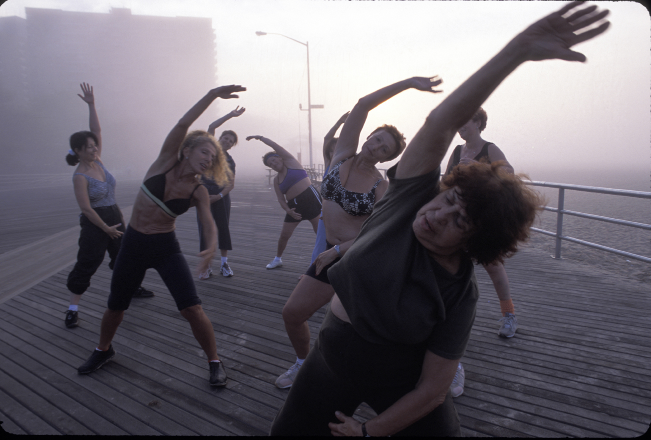 Women stretch on the boardwalk in Coney Island, NY on the one year anniversary of 9/11 on September 11, 2002.