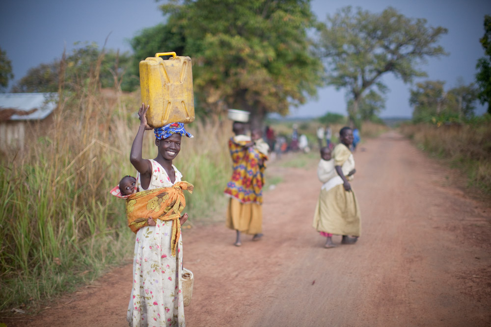 A villager carries water from a Clearwater Initiative well back to her home.