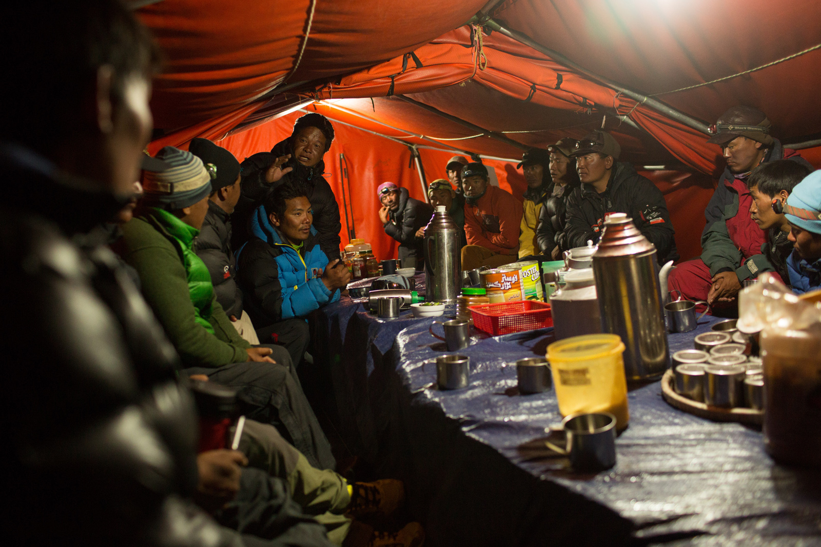 Climbing Sherpas huddle together in a mess tent to decide who will make the last runs across the Khumbu Ice Fall to collect the gear from Camp 2, 3, and 4, and also who will attempt a body rescue just below the summit.