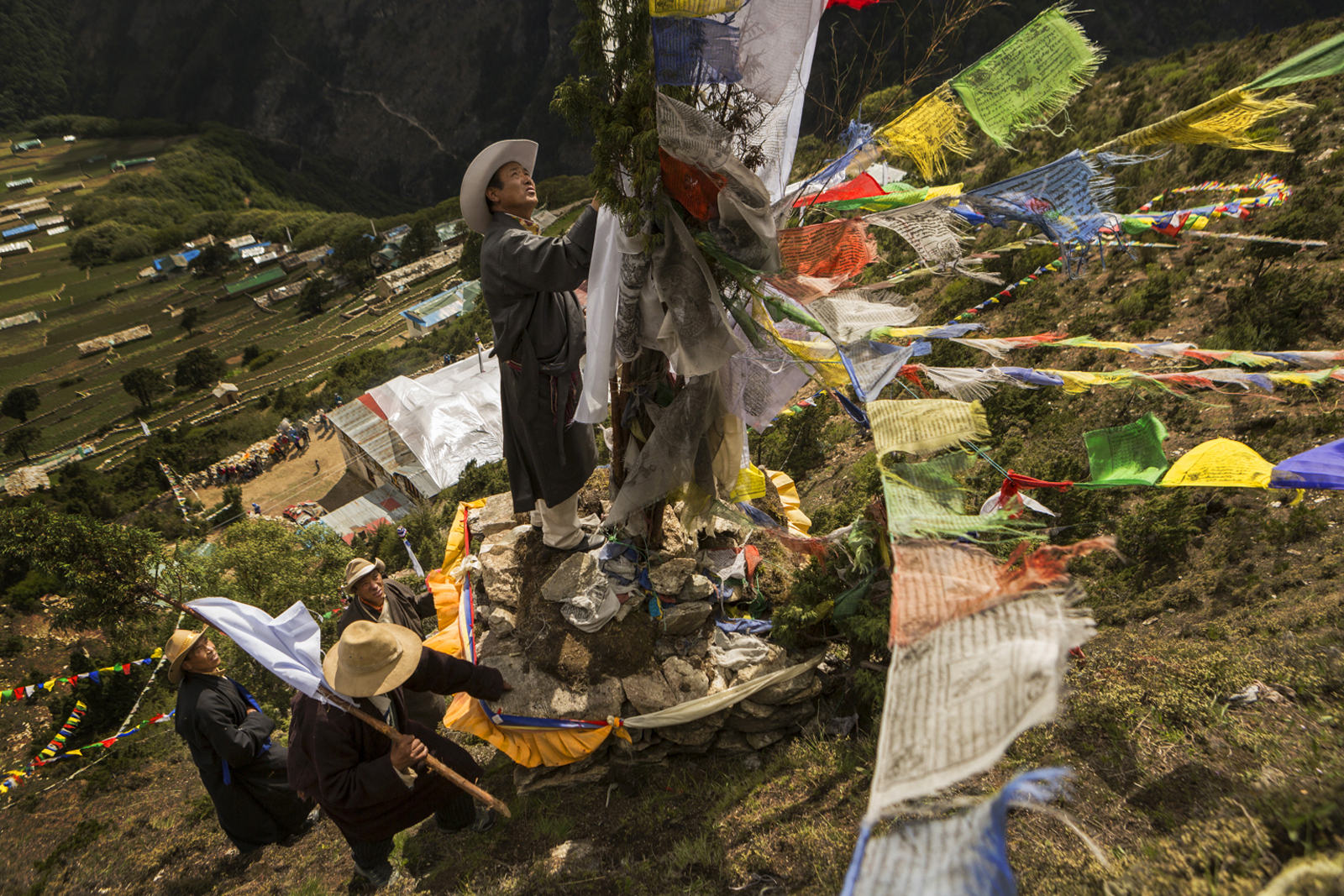 Organizers (eldest males from the 6 families) of the Dumji Festival do the {quote}opening ceremony{quote} in which they take prayer flags (white) and chang to a high puja altar for the God of the Khumbu (Kumbuyula).   The flags and juniper branch are tied to the altar.
