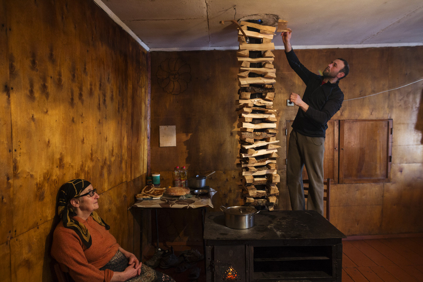 Misha Mchedliani stacks firewood to dry around the chimney of his family's stove in the village of