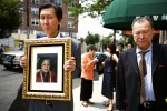 Two brothers mourn their mother at the end of her traditional Buddhist funeral. As part of a Buddhist tradition of honoring those who live to 100, her picture is paraded along with her coffin outside of the funeral home.