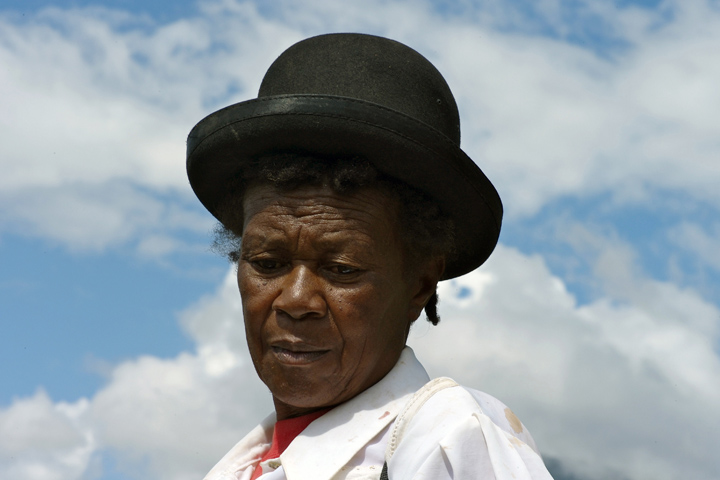 It is a head and shoulders photograph of a 71-year old Afro-Bolivian woman wearing a bowler hat, against the backdrop of a blue sky.