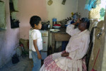 Exhausted from working in the field Ms. Vasquez talks with her grandson.