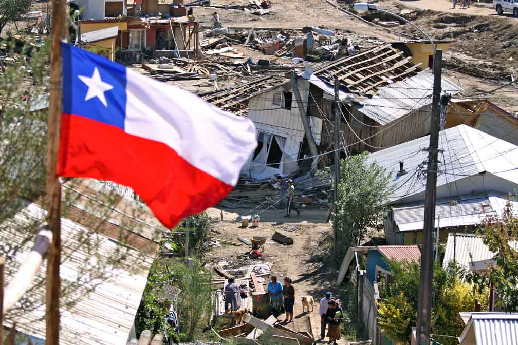 A Chilean flag is pictured in the foreground against a backdrop of damaged homes.