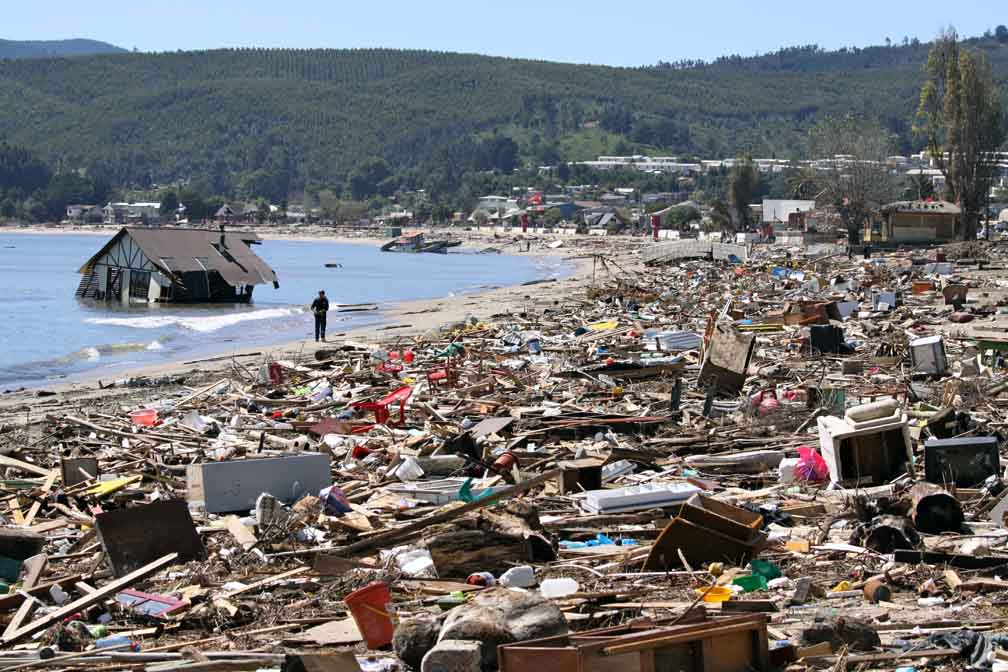 A lone individual is seen walking in a wide-angle shot showing a badly littered beachfront; a house sits in the sea.