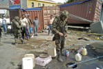 March 5, 2010 - A Chilean soldier examines a gas tank where the detained men in the background were illegally siphoning gasoline; the men were released after a warning.