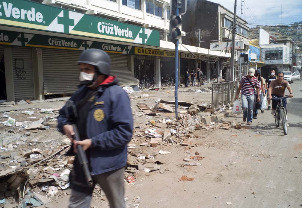 A policeman carrying a shotgun walks, towards the camera, down a heavily damaged street.