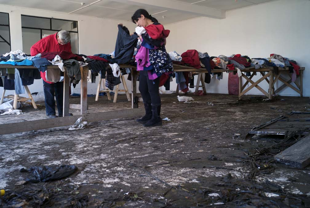 A middle-aged woman and man stand in a large room (used as a donation center) examining clothing; piles of clothes are on several wood tables.