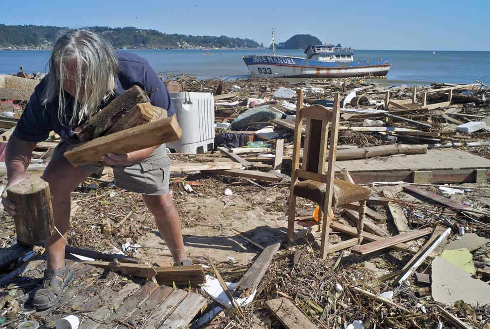 A 65-year old man, with long grey hair and wearing shorts, collects wood from a beach clutter with debris from a tsunami.