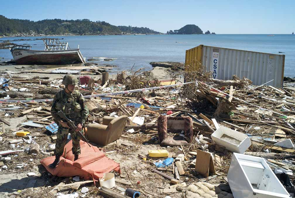 March 8, 2010 - A soldier guards a container, washed ashore by a tsunami, filled with toxic chemicals.