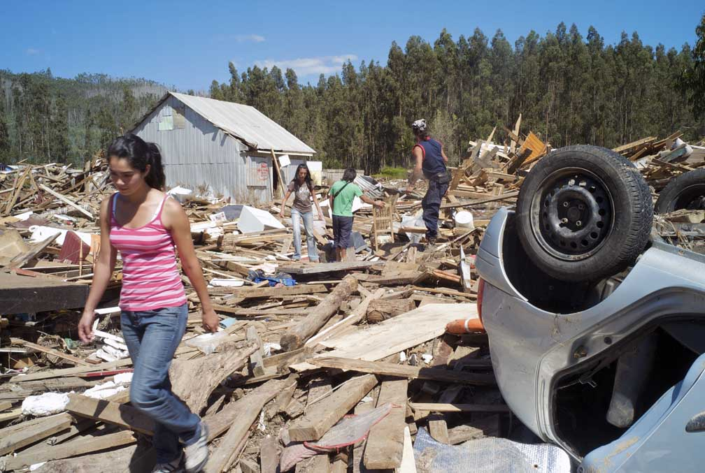 A young woman, in the foreground of a debris-filled landscape, walks pass an overturned car.