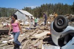 March 8, 2010 - Residents walk through the debris-filled streets.