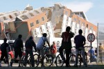 March 4, 2010 - Chileans view an apartment building which was toppled by an 8.8-magnitude earthquake. According to the investigative police (PDI - Policia de Investigaciones) seven were killed in the collapse and six missing.