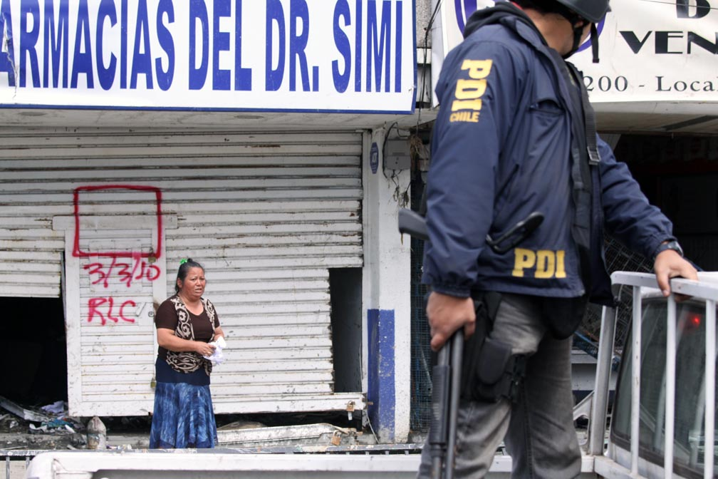 A policeman holding a shotgun turns around to look at a Chilean woman standing across the street.