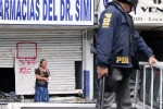 March 5, 2010 - A Chilean policeman observes a woman as she complains about being accused of looting.
