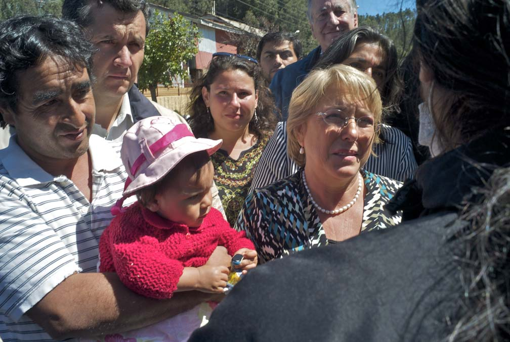 In a tightly framed crowd shot, Chilean president Michelle Bachelet stands in the middle speaking to a resident whose back is to the camera.