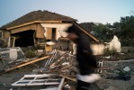 The blurred image of a young man is shown as he walks pass a heavily damaged house and its debris-filled front yard.