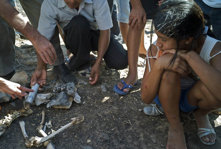 Amazonians examine a tear gas canister found on charred grounds where indigenous natives and local migrants clashed with Peruvian national police. The bones they said were found on these grounds and are an Amazonian citizen killed by the police.