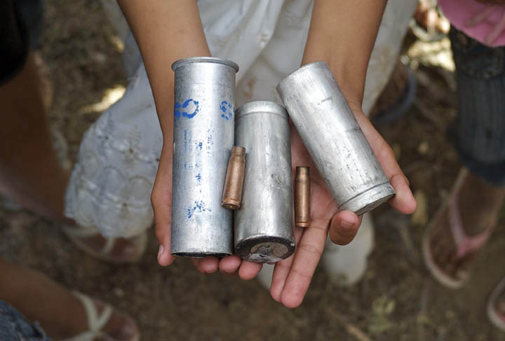 An Amazonian girl holds empty tear gas canisters and bullet shells she found on charred grounds where indigenous natives and local migrants clashed with Peruvian national police.