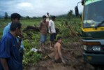 After a heavy rainfall, a group of Awajun men contemplate how to extract their vehicle from mud.