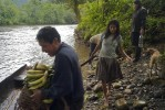 Awajun farmer and landowner Ricardo Apanu Nampin, 53, left, Ana Egampash Wakiu, 35, center, and Mirsa Wachapa, 40, prepare to cross the Chiriaco river with the day's harvest.