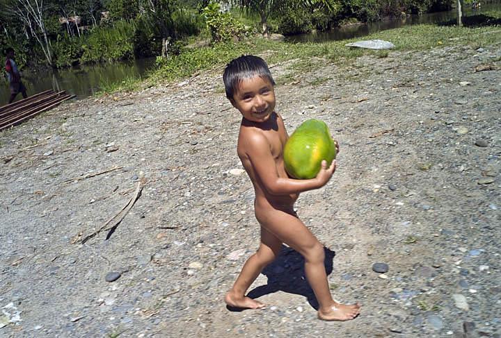 A young Awajun boy carries a papaya from his father's canoe.