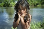 A wet ten-year old girl holds her hands to the lower part of her face and stares into the camera, shortly after exiting a river which is in the background.