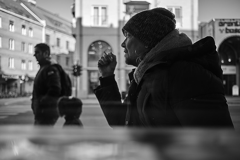 On a cold afternoon a man smokes a cigarette outside a cafe.