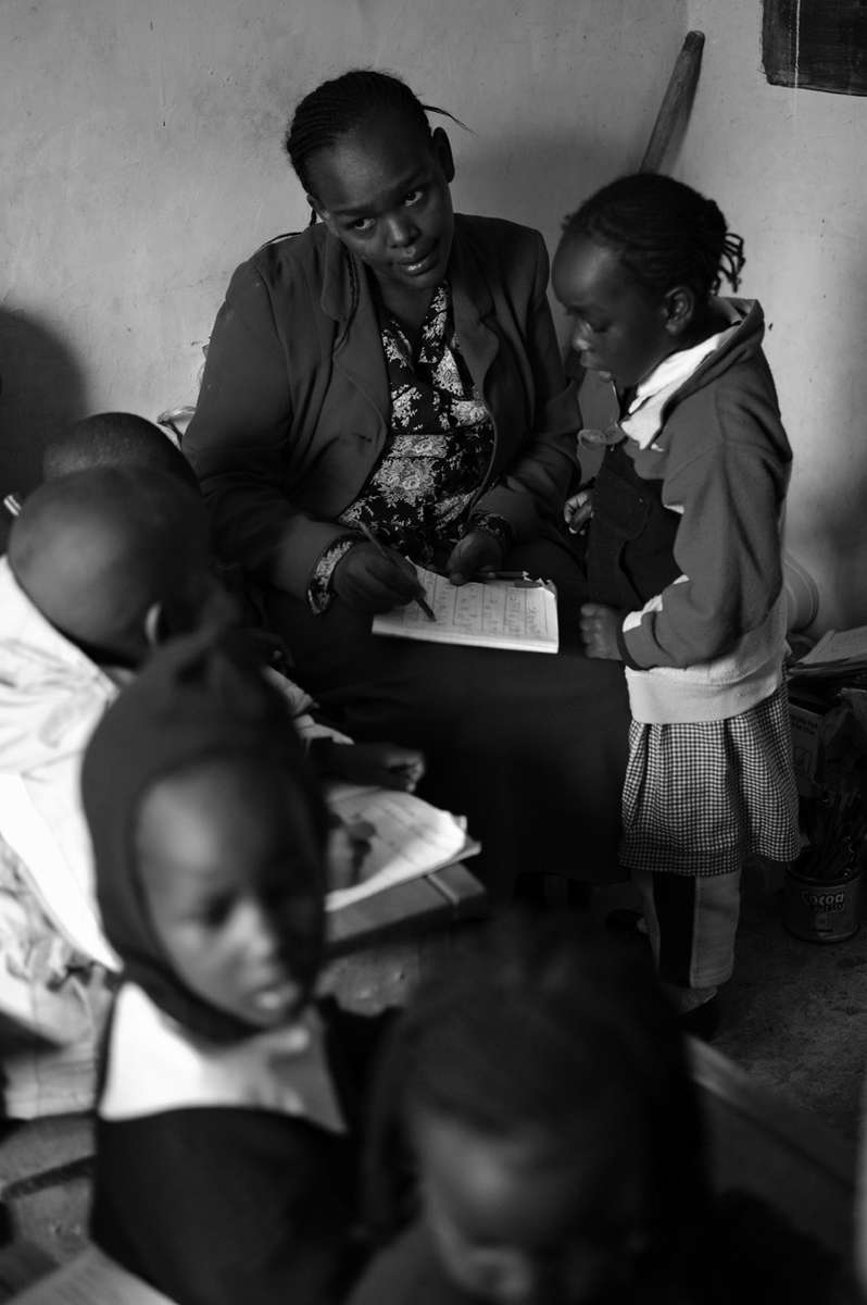 While testing a student's reading abilitynursery teacher Cecilia Muringi eyes a student who is not behaving properly.
