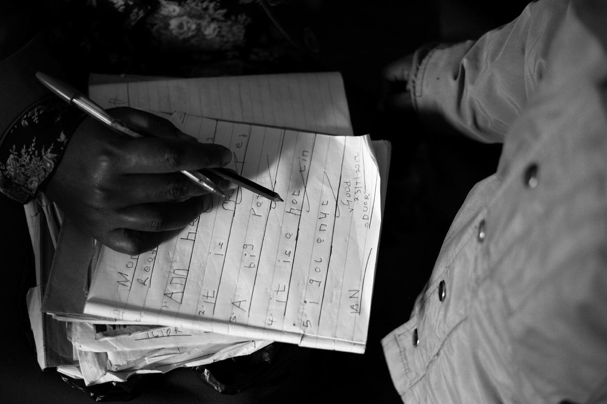 Nursery school teacher Cecilia Muringi checks a student's homework and reading ability.