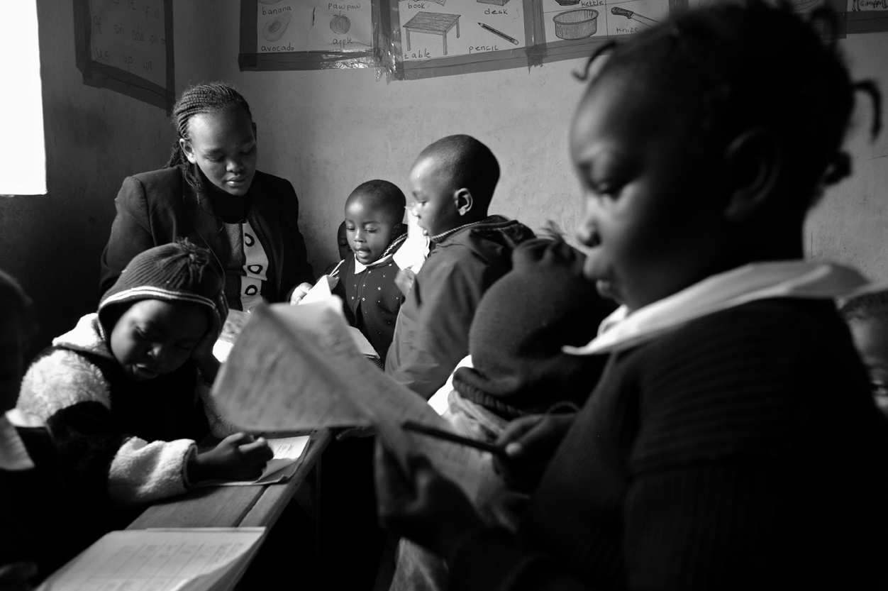 Cecilia Muringi reviews the just completed work of her nursery school students as she has them read from their notebooks.