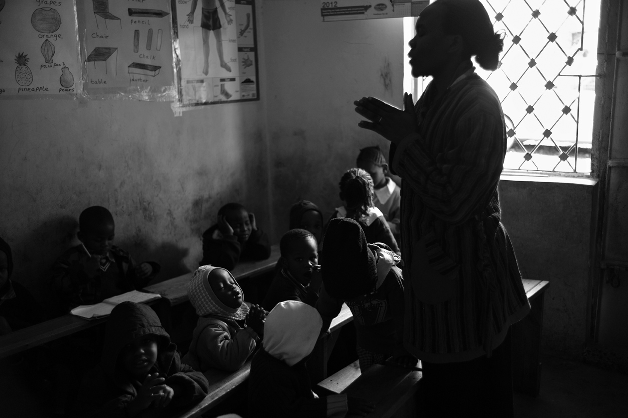 Nancy Vivian Obanda leads her baby class students in prayer before their snacks are distributed.