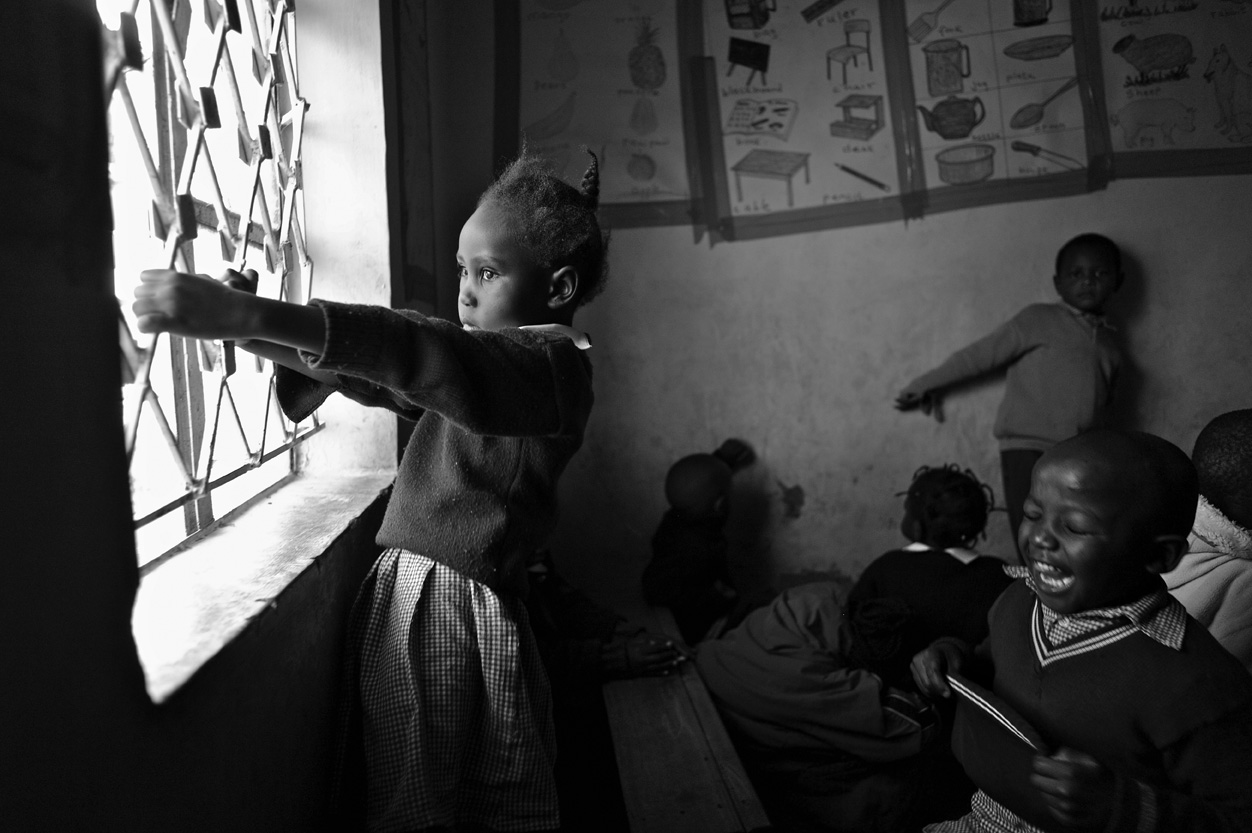 Nursery school students play while their teacher, at the front of the room, administers a test to three students at a time. {quote}I can't test the entire class at once because they would just play with, tear or stain the paperwork,{quote} says Cecilia Muringi.