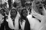 Women dressed in traditional capes watch and sing as a procession carrying a painting adorned with the image of Our Lord of Miracles arrives.