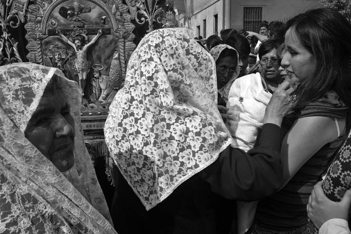Women dressed in traditional capes offer blessings to those following the procession of Our Lord of Miracles.